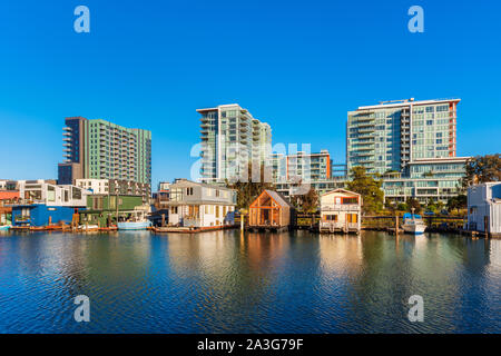 Houseboats on Mission Creek Channel in Mission Bay district in San Francisco, California, USA. Newly developed apartment flats in the background. - Stock Photo