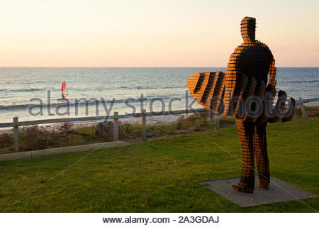 Sculpture of a surfer by April Pine entitled 'Pause' and a view to a windsurfer at sunset, South Cottesloe Beach, Western Australia - Stock Photo
