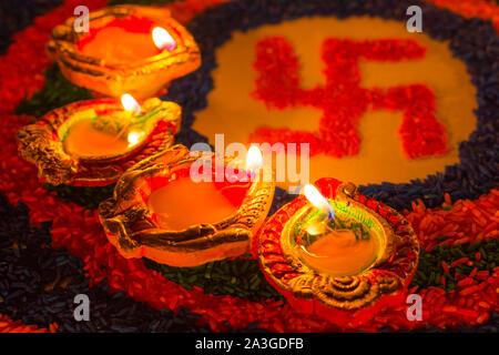 Indian festival Diwali, Diya oil lamps lit on colorful rangoli with Swastika symbol. Hindu traditional. Happy Deepavali. - Stock Photo