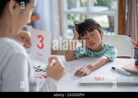 tired and bored toddler while studying with mother at home - Stock Photo