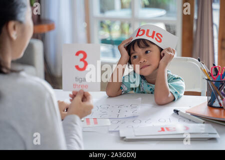 kid enjoy learning number and word using flashcard with mother at home - Stock Photo