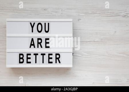 'You are better' words on a lightbox on a white wooden background, top view. Overhead, from above. Flat lay. Copy space. - Stock Photo