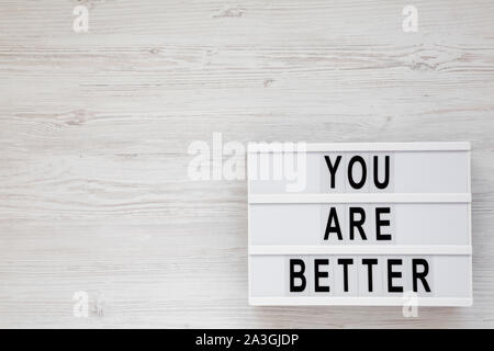 'You are better' words on a lightbox on a white wooden surface, top view. Overhead, from above. Flat lay. Space for text. - Stock Photo