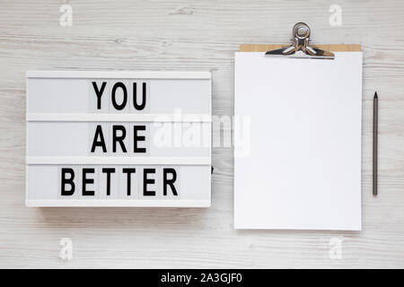 'You are better' words on a lightbox, clipboard with blank sheet of paper on a white wooden surface, top view. Copy space. - Stock Photo