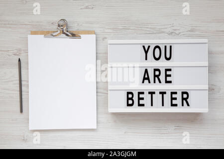 'You are better' words on a lightbox, clipboard with blank sheet of paper on a white wooden surface, top view. Overhead, from above, flat lay. - Stock Photo