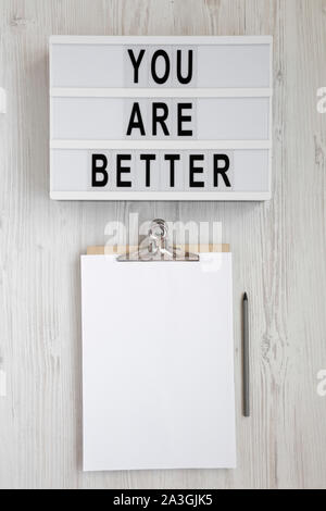'You are better' words on a lightbox, clipboard with blank sheet of paper on a white wooden background, top view. Overhead, from above, flat lay. - Stock Photo