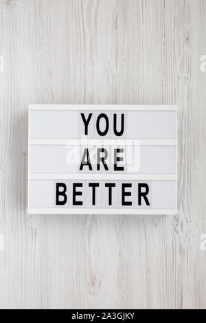 'You are better' words on a lightbox over white wooden surface, top view. Overhead, from above. Flat lay. - Stock Photo