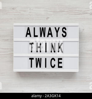 'Always think twice' words on a modern board on a white wooden background, top view. Overhead, from above, flat lay. - Stock Photo