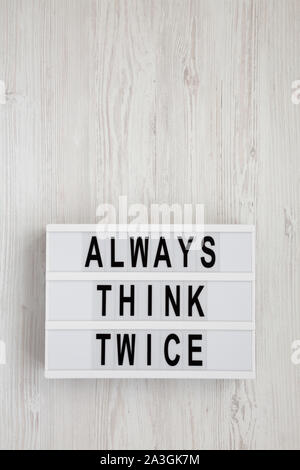 'Always think twice' words on a lightbox on a white wooden background, top view. Overhead, from above, flat lay. Space for text. - Stock Photo
