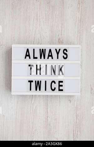 'Always think twice' words on a modern board on a white wooden surface, top view. Overhead, from above, flat lay. - Stock Photo