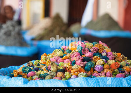 Multicolored dried flowers, used for soaps and perfumes, on sale in the souks of Marrakesh's medina area in Morocco. - Stock Photo