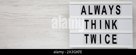 'Always think twice' words on a lightbox on a white wooden surface, top view. Overhead, from above, flat lay. Copy space. - Stock Photo