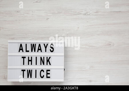 'Always think twice' words on a modern board on a white wooden surface, top view. Overhead, from above, flat lay. Copy space. - Stock Photo