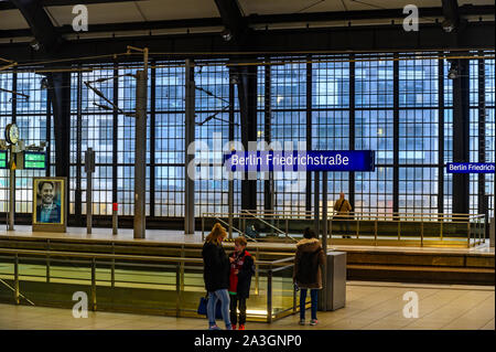 Berlin, Germany - October 8, 2019: View to the rail station Friedrichstrasse in the center of Berlin with passengers and his glass facade in the backg - Stock Photo