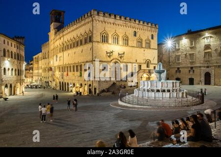 People at dusk in Piazza IV Novembre, fountain Fontana Maggiore in front of Palazzo dei Priori, Perugia, Umbria, Italy - Stock Photo