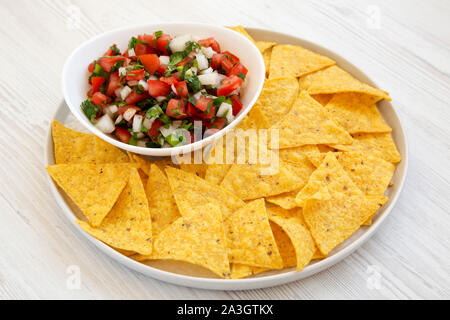 Pico de Gallo with gluten free tortilla chips on a white wooden background, side view. - Stock Photo