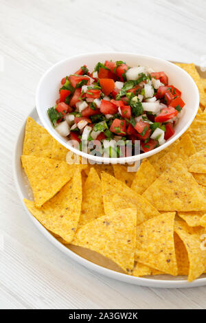 Pico de Gallo with gluten free tortilla chips on a white wooden surface, side view. Close-up. - Stock Photo