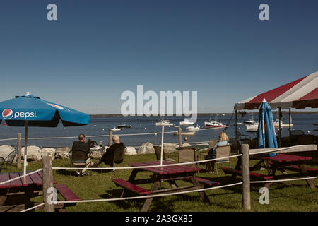 Lincolnville, Maine - September 27th, 2019:  People enjoying views of Lincolnville beach at a lobster shack in Lincolnville, Maine on a Fall day. - Stock Photo