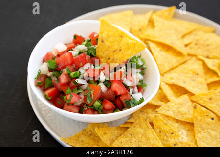 Pico de Gallo with gluten free tortilla chips on a black background, side view. Closeup. - Stock Photo