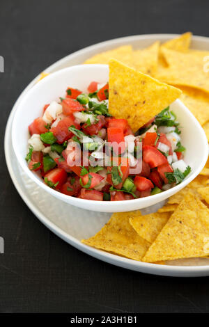 Pico de Gallo with gluten free tortilla chips on a black surface, side view. Close-up. - Stock Photo