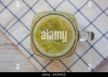 Homemade green cucumber apple smoothie in a glass jar, top view. Flat lay, overhead, from above. Close-up. - Stock Photo