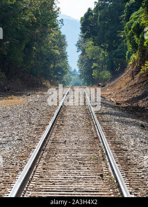 Railroad tracks leading off into the distance - Stock Photo
