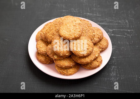 Cereal cookies on a pink plate on a black surface, side view. Closeup. - Stock Photo