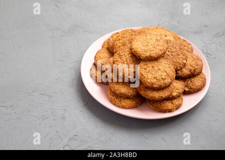 Cereal cookies on a pink plate on a gray surface, side view. Copy space. - Stock Photo