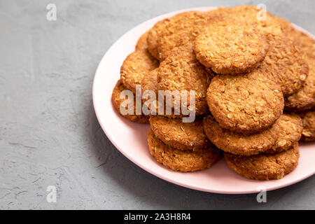 Cereal cookies on a pink plate on a concrete background, side view. Copy space. - Stock Photo