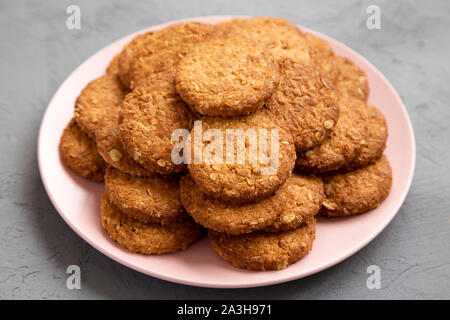 Cereal cookies on a pink plate on a concrete surface, side view. Close-up. - Stock Photo