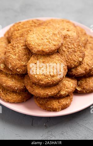 Cereal cookies on a pink plate on a gray surface, low angle view. Close-up. - Stock Photo
