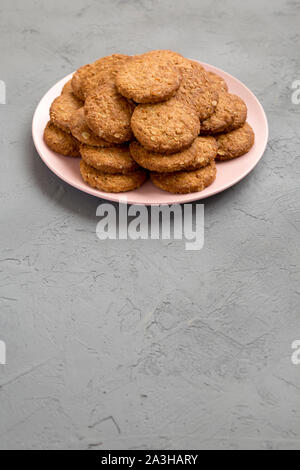 Cereal cookies on a pink plate on a gray background, low angle view. Copy space. - Stock Photo