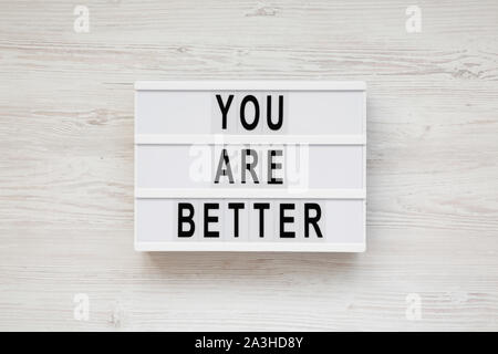 'You are better' words on a lightbox over white wooden background, top view. Overhead, from above. Flat lay. - Stock Photo