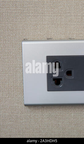 Grey universal electricity sockets plug on a yellow wall. - Stock Photo