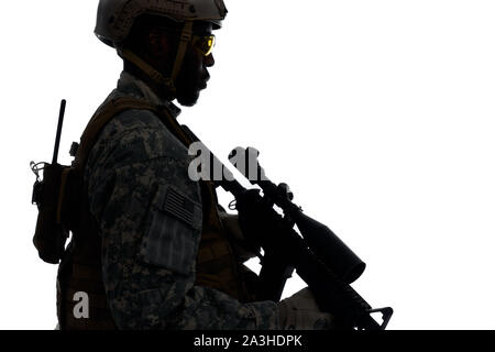 Silhouette of male soldier wearing Americans army uniform and helmet protecting homeland. Man holding weapon machine in hands and looking at side. White studio background. - Stock Photo