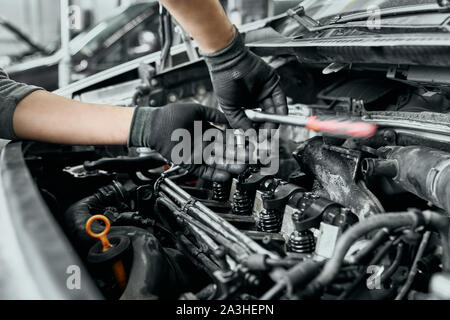 Qualified man in black dirty gloves unscrews old spark plugs from car engine by wrench to change them into new ones.Auto mechanic proficiently performs his basic functions in service center - Stock Photo