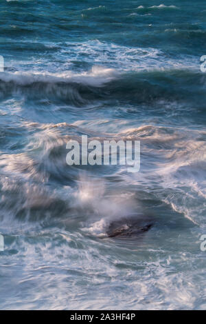 Long exposure of waves and the incoming tide splashing onto a rocky beach - Stock Photo
