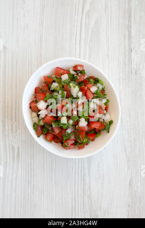 Pico de Gallo in a white bowl on a white wooden surface, top view. Overhead, from above, flat lay. - Stock Photo