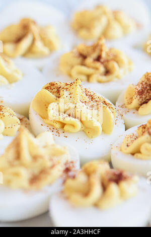Delicious deviled eggs appetizers sprinkled with paprika for Easter. Selective focus on center egg with extreme blurred foreground and background. - Stock Photo