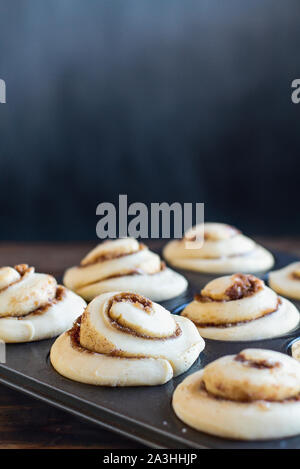 Fresh made homemade tall cinnamon roll rising in a muffin tin. Extreme selective focus with blurred foreground and background. - Stock Photo
