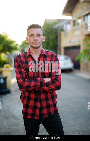 Young man wearing red checkered shirt in the streets outdoors - Stock Photo