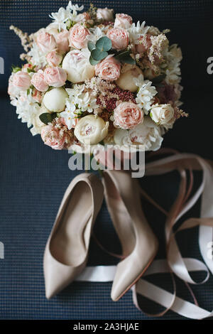 Composition from the bridal bouquet of beautiful peonies flowers with a pair of modish bridal shoes on a dark blue background. Concept of wedding