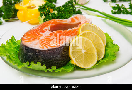 Salmon fish with lemon and sauce lies on lettuce