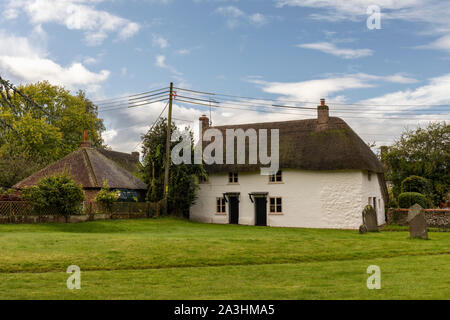 A white thatached cottage in the grounds of St James church, Avebury, Wiltshire, England - Stock Photo