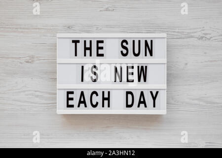 'The sun is new each day' words on a lightbox on a white wooden background, top view. Overhead, from above, flat lay. - Stock Photo