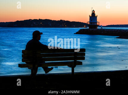 SOUTH PORTLAND, ME - SEPTEMBER 13: A man watches the sunrise, off the Maine coast, near Spring Point Ledge Lighthouse in South Portlland, Maine , . (© - Stock Photo