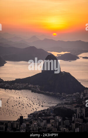Beautiful sunrise view from Corcovado Mountain to the Sugar Loaf, city and ocean, Rio de Janeiro, Brazil - Stock Photo