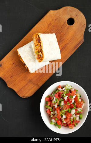 Homemade chorizo breakfast burritos with pico de gallo on a black background, top view. Flat lay, overhead, from above. - Stock Photo