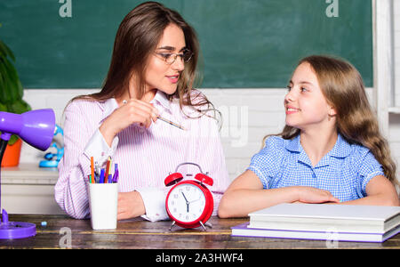 Its time to back to school. Teacher and little child at lesson. Pretty woman and small girl in school. During class time. School time. Private teaching. Education. - Stock Photo