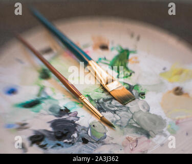 Paint brushes mixing paint on artist palette in muted colors pastels - Stock Photo
